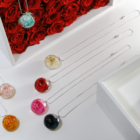 Aranżacja naszyjników Rose Belle w różami wiecznymi w tle